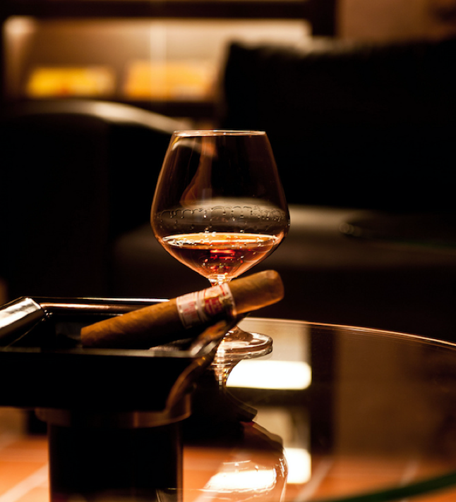 Brandy and a Havana House cigar on a glass table in a cigar lounge