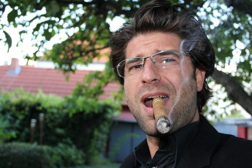 Man smoking a cigar lit by a Xikar lighter.