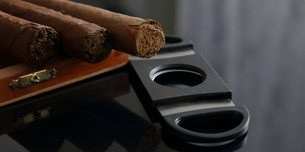 Three cigars with a cigar cutter on a black surface