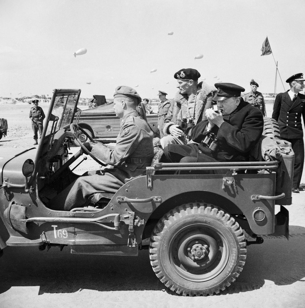 Winston Churchill lights cigar in the back of a Jeep.