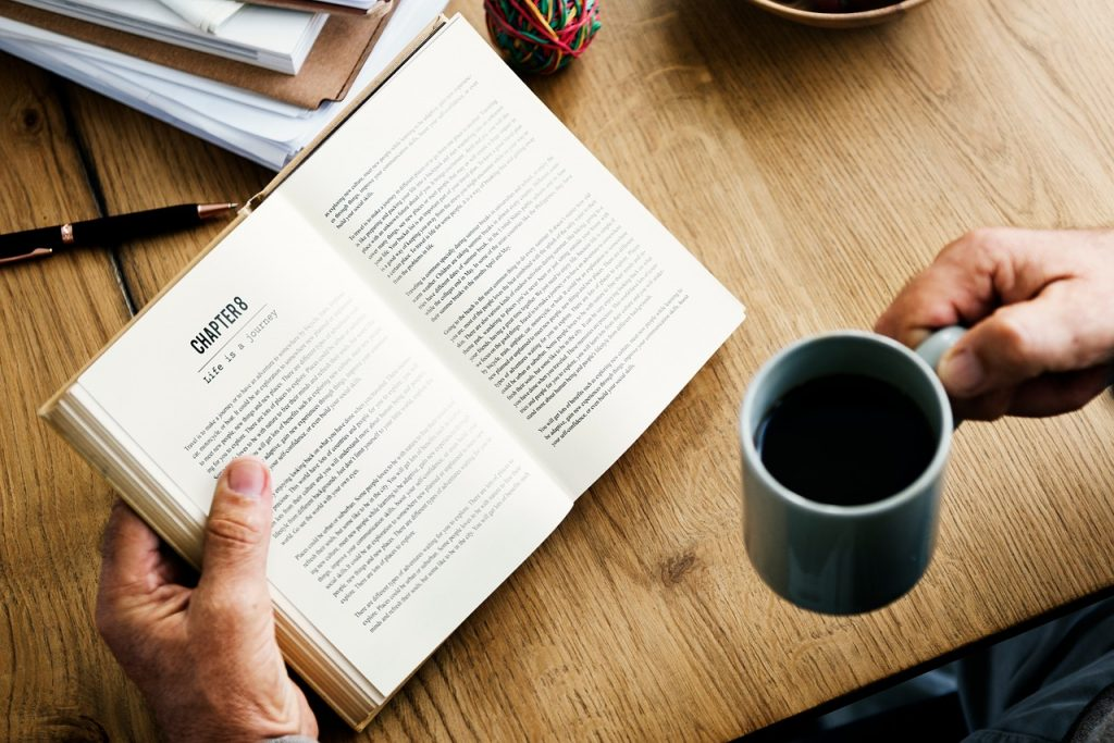 Man reads a book with a mug of coffee.