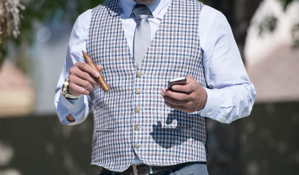Gentleman looks up guide for preparing a cigar.