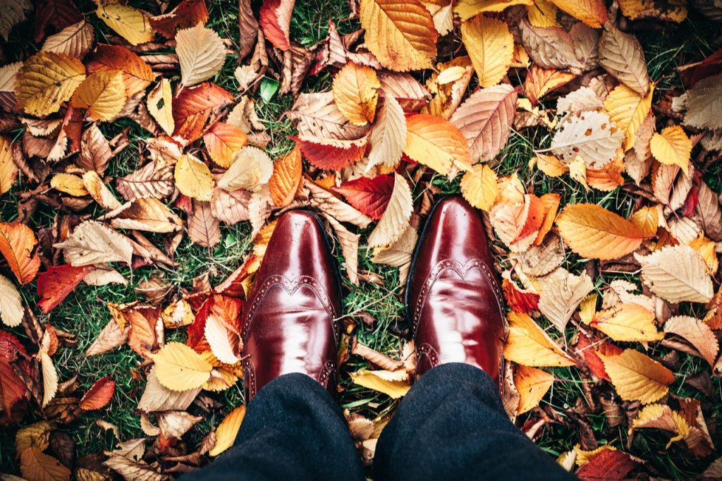 Gentleman in brogues walks through autumn leaves.