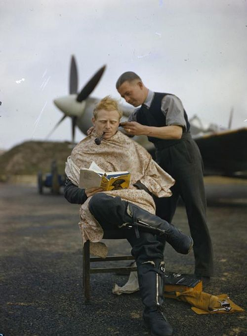 RAF pilot gets a shave while having a smoke