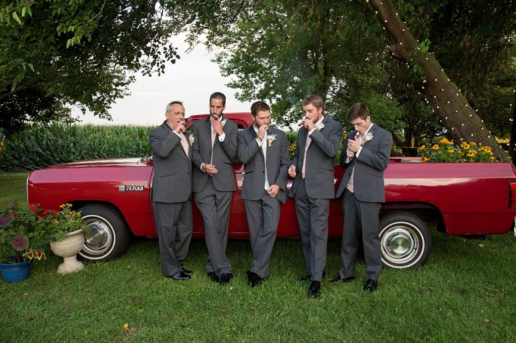 Groomsmen enjoy some fine cigars during a wedding.