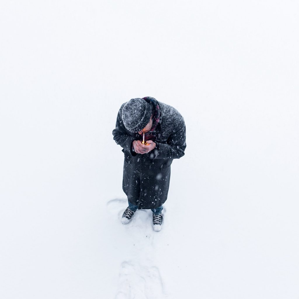 a man smoking a cigar outside in winter