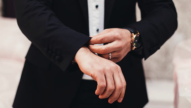 Man wearing suit and watch pulling down his sleeve.