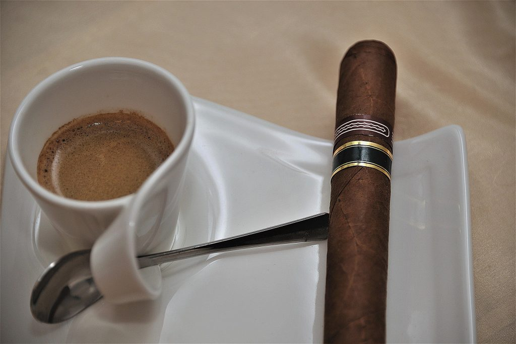 A cup of Cuban coffee with a cigar