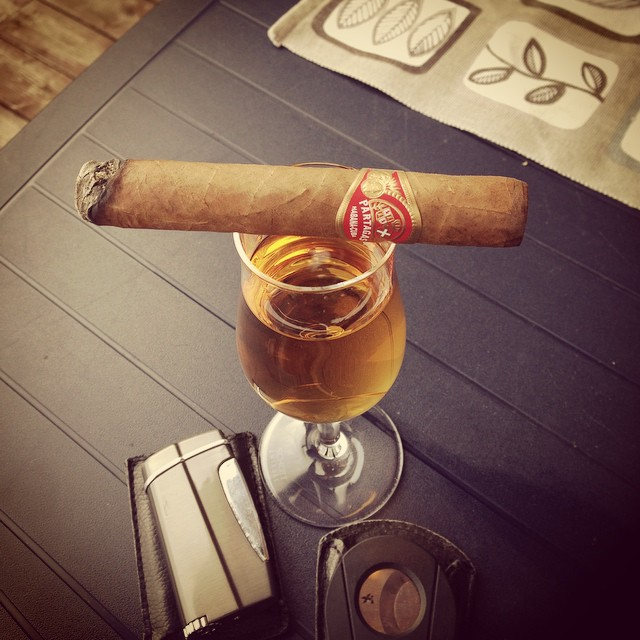 A cigar, cutter, lighter and glass of whisky