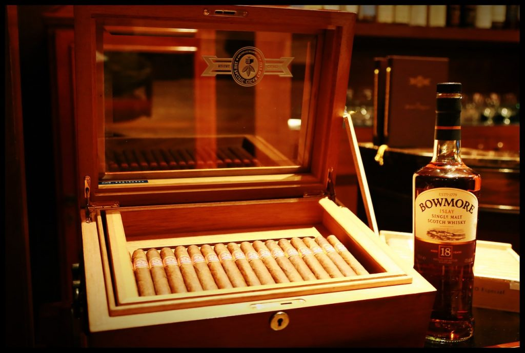 An open cigar box with a bottle of Scotch whisky.