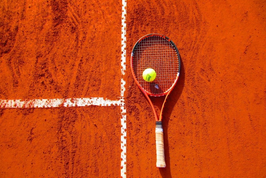 A tennis racket and ball on an orange tennis court