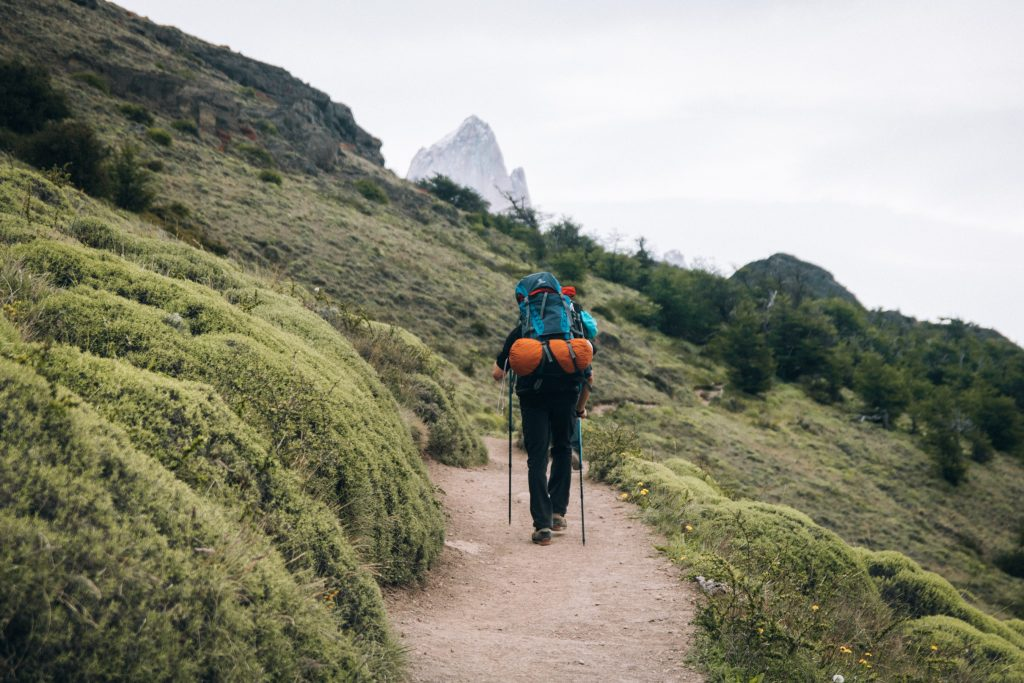 A man with a backpack and sticks hiking along a mountain path