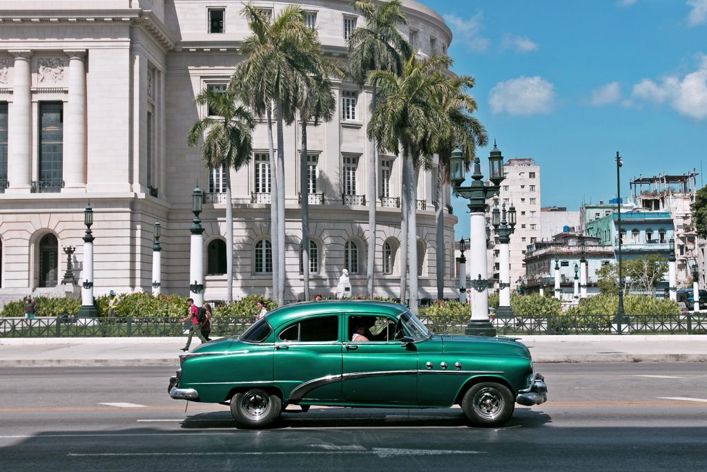 Travel Destinations for Cigar Lovers: A green car driving on a street in Havana