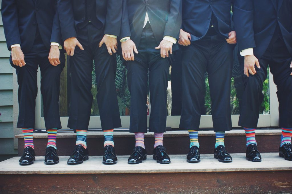 Five men in suits pulling up their trousers to reveal stripy socks