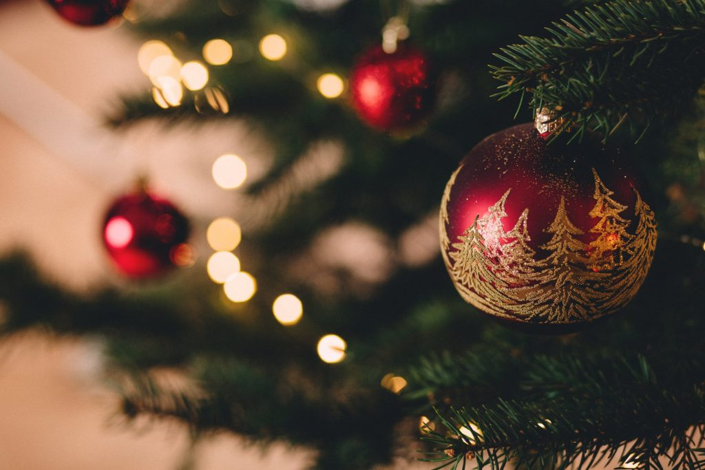 A red bauble featuring glittery golden Christmas trees hung on a larger tree