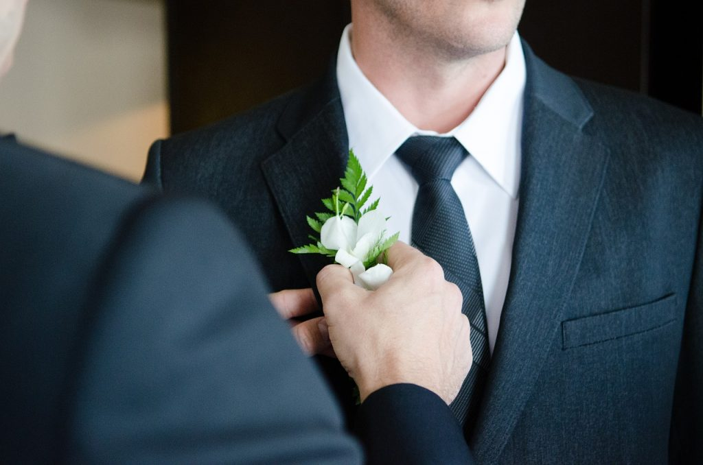 A best man pinning a flower to the groom on his wedding day