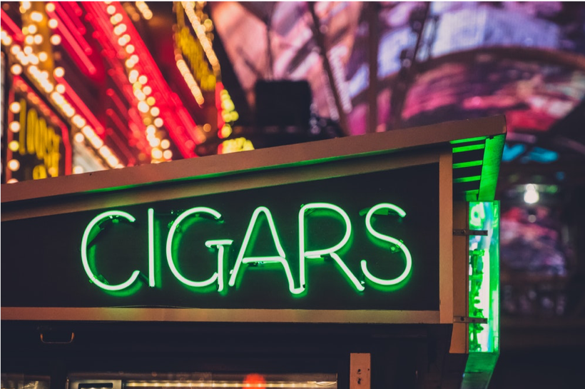 Neon signage on the side of a shop that reads cigars