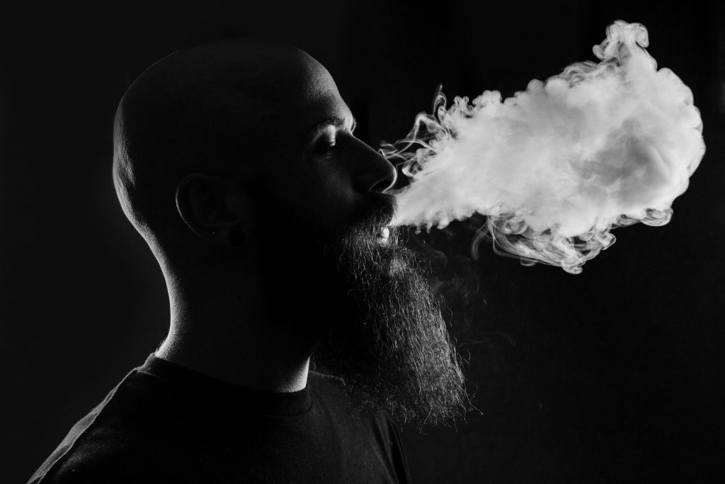 A man with a large beard blowing smoke out through his mouth