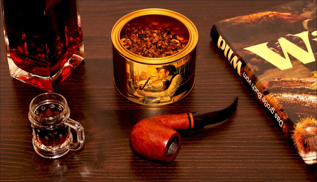 Smoking pipe on a table with tobacco, a book and two glasses of drink