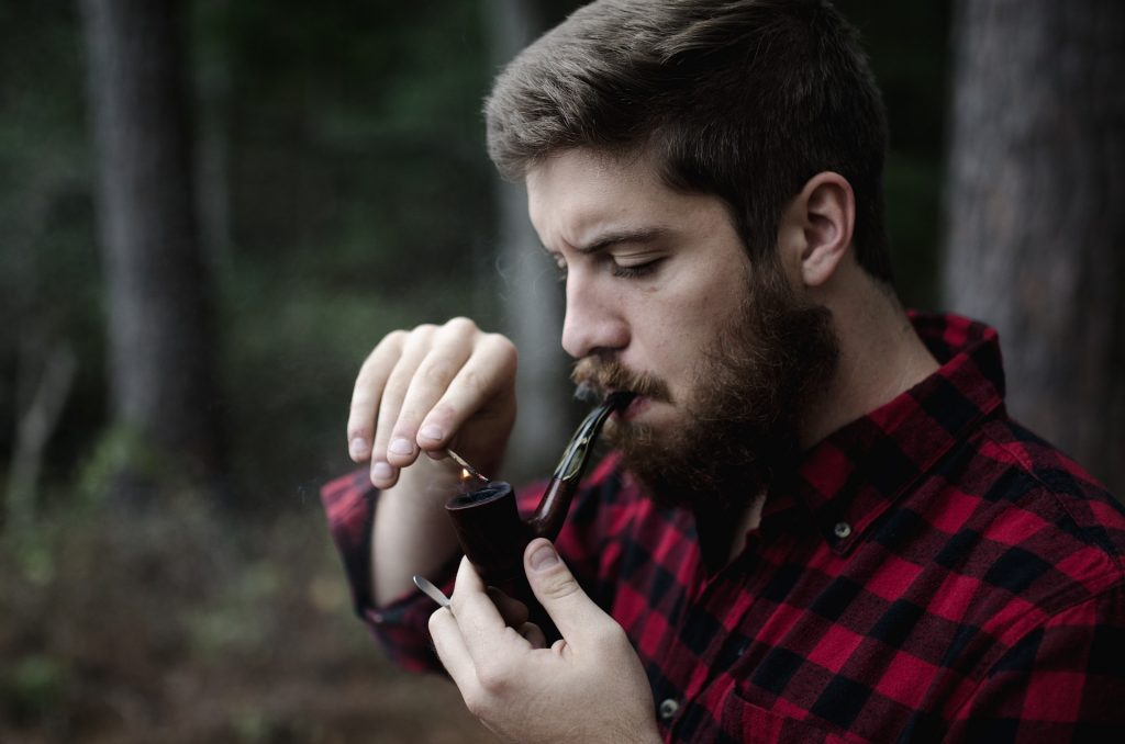 Man outdoors lighting a smoking pipe