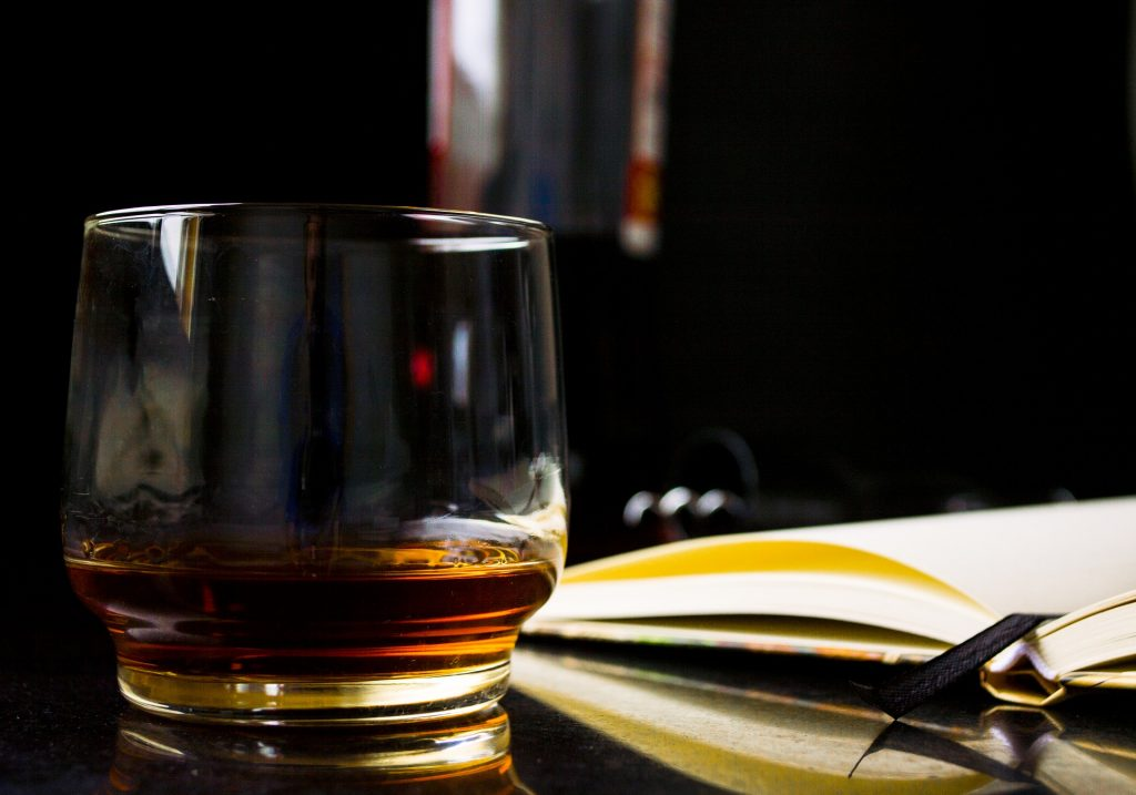Glass of whiskey next to a book