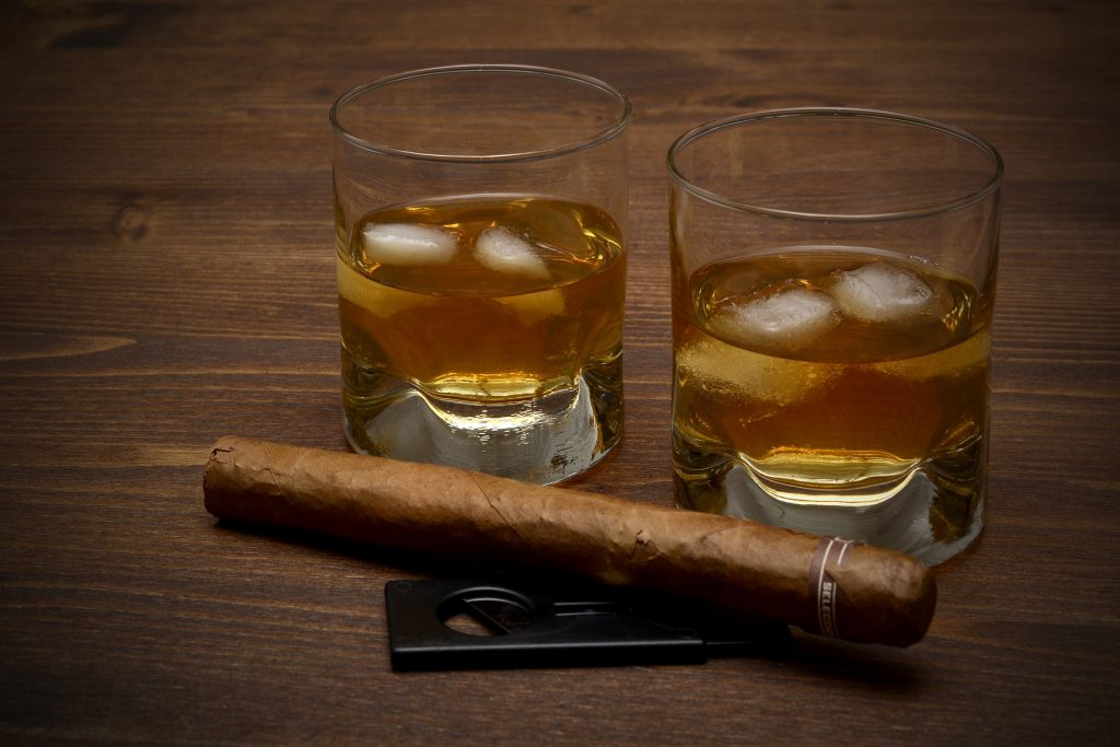 Two glasses of whisky with cigar and cigar cutter