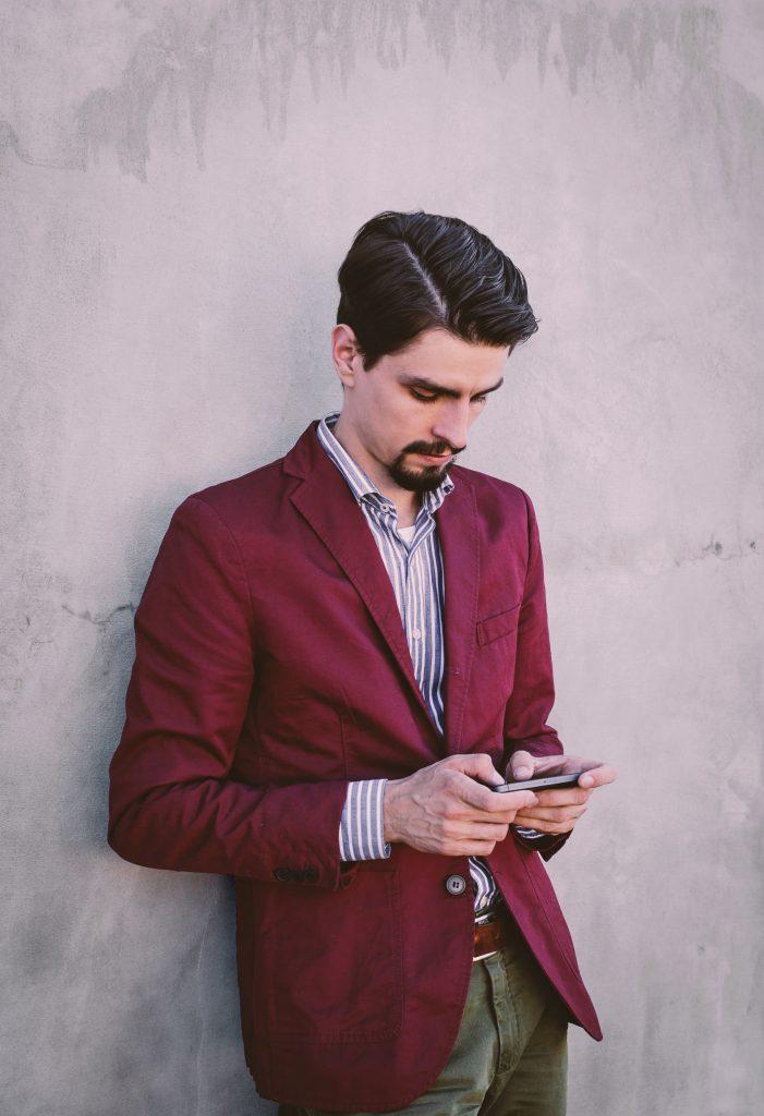 Man wearing red blazer on phone