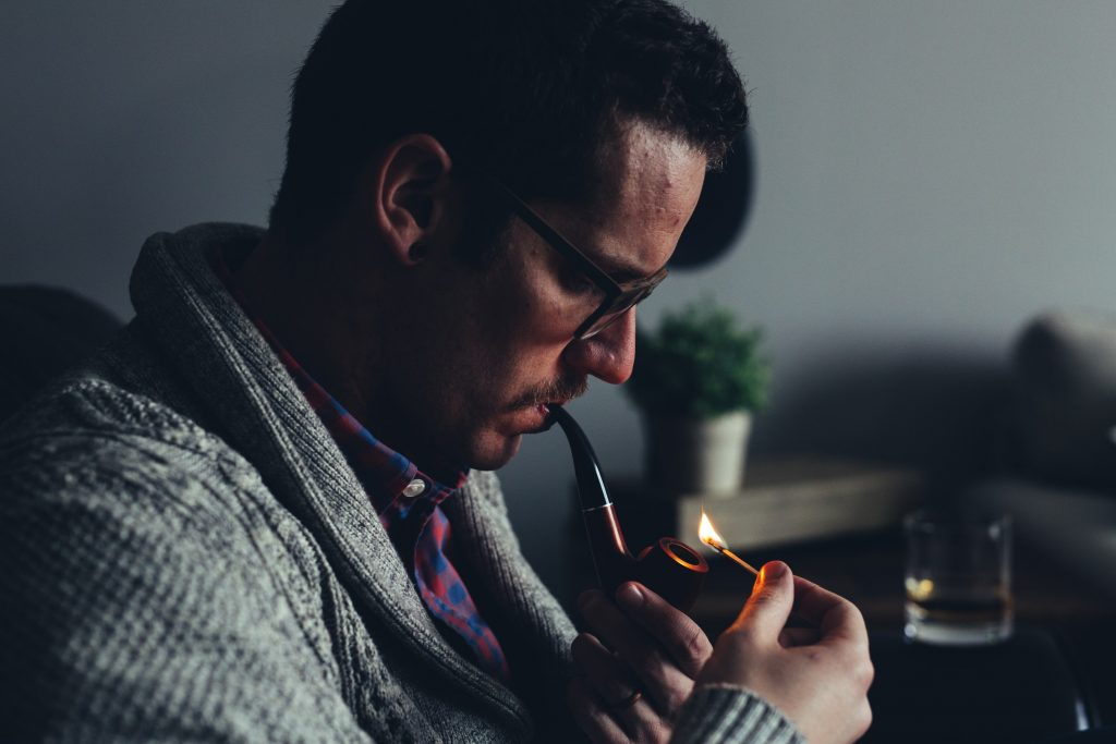 a man lighting a tobacco pipe with a match