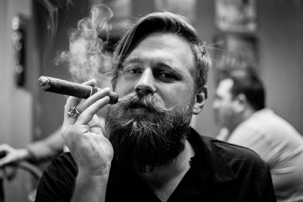 Man with beard smoking cuban cigar