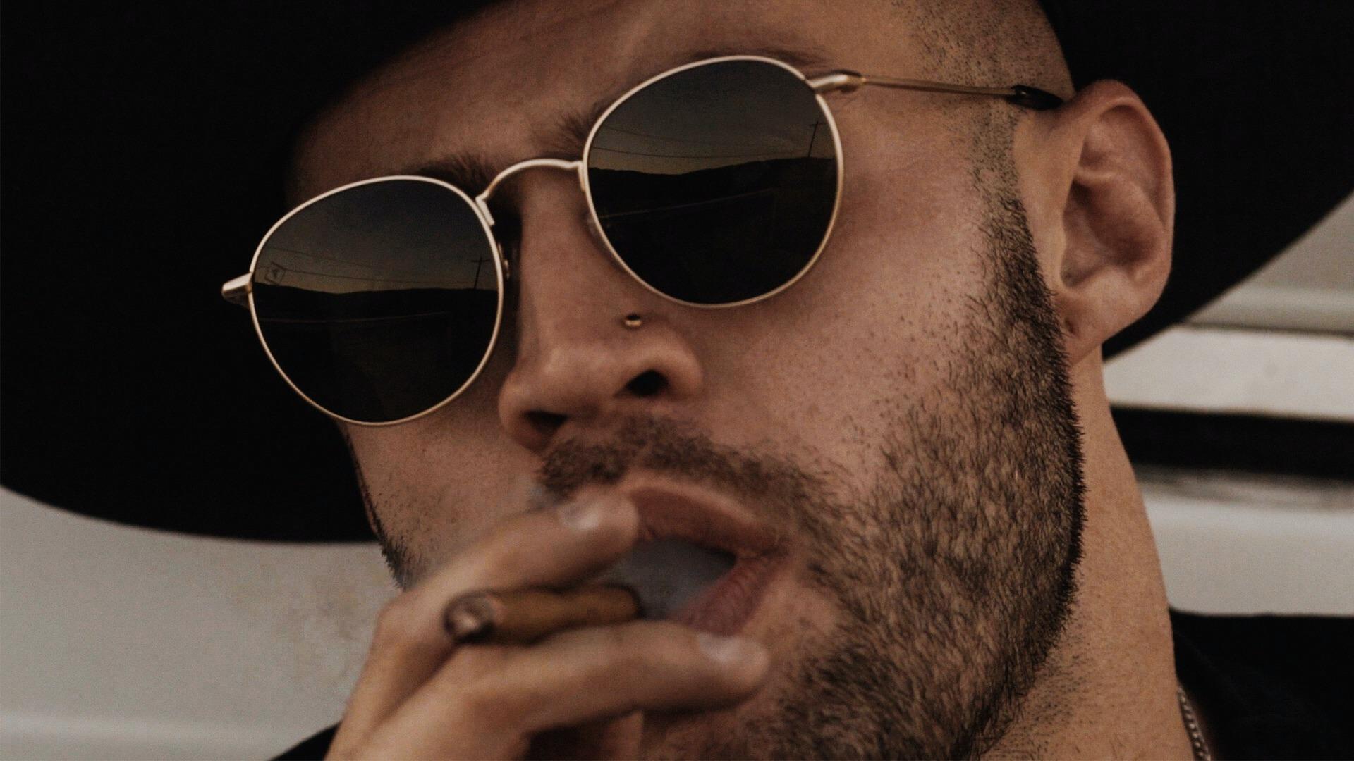 Man with sunglasses smoking a cigar