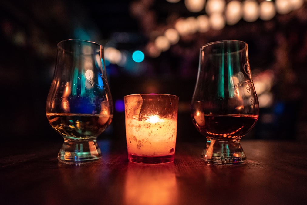 Two whisky glasses with a candle