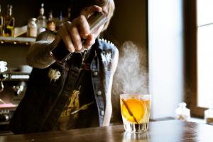Person spraying smoke on whisky