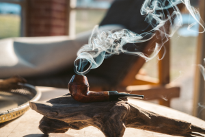 Smoking pipe packed with tobacco resting on an ashtray