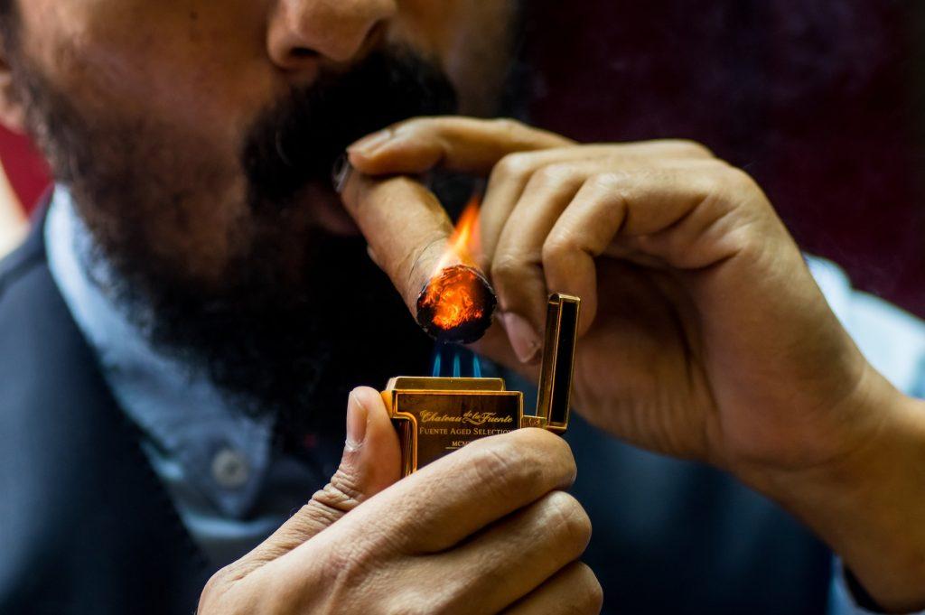 Man wearing suit lighting a cigar