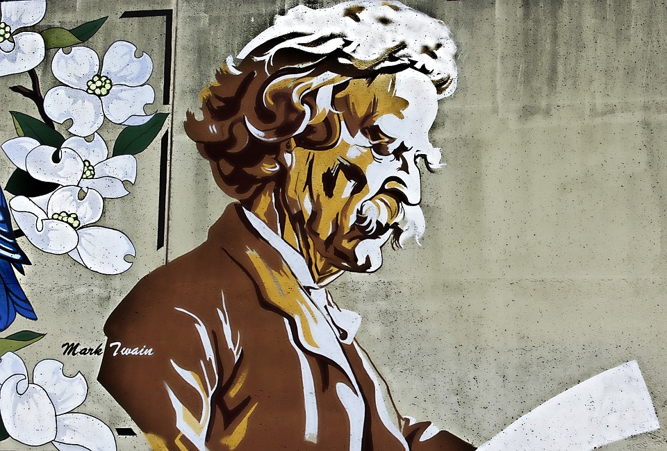 A painting mural of Mark Twain reading surrounded by flowers