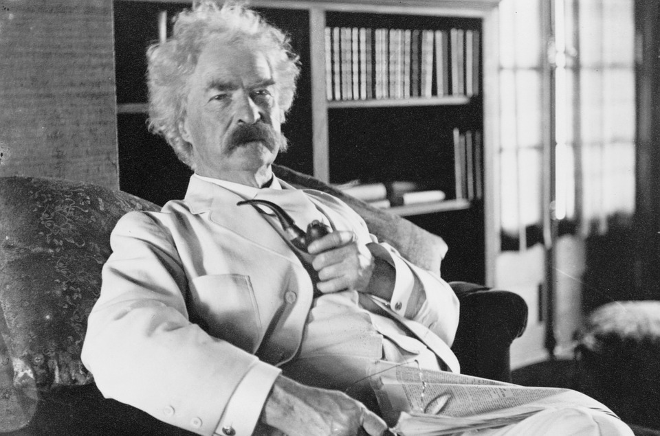 Mark Twain in a white suit with a smoking pipe