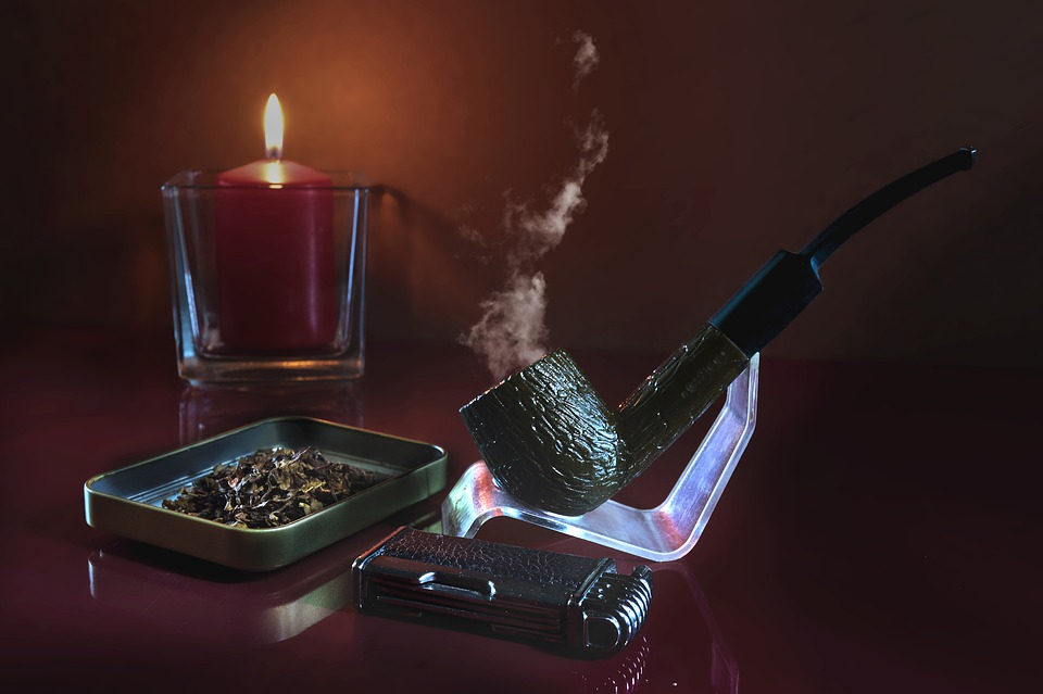 A smoking pipe on a stand with dry tobacco and a candle