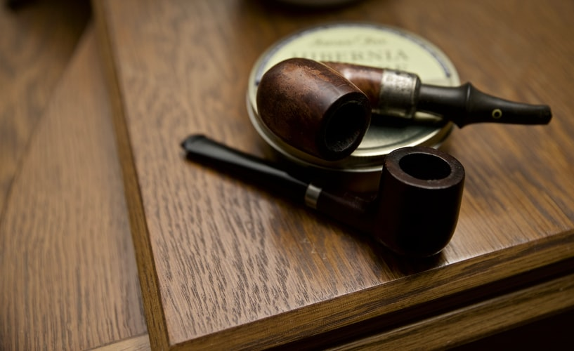 Two old authentic wooden smoking pipes with a tobacco case