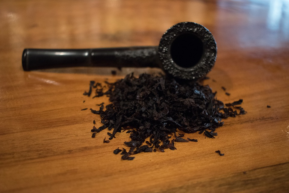 A black smoking pipe with tobacco