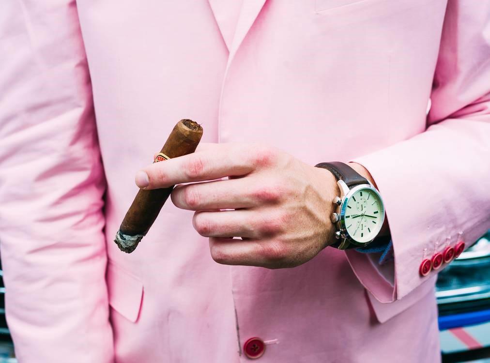 man wearing a pink jacket holding a cigar