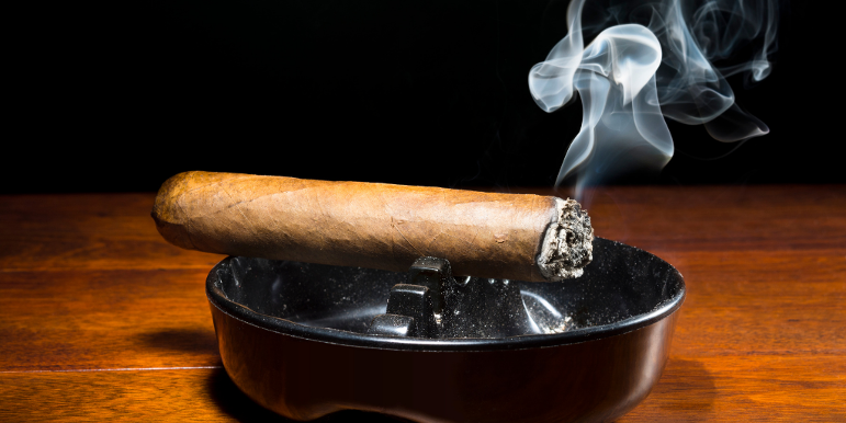 A cigar burning out in an ashtray