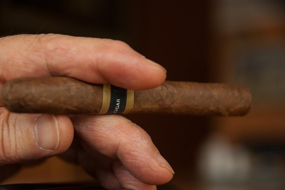 A hand holding a thin cigar