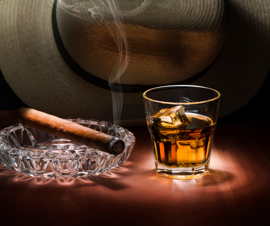 A cigar next to a glass of rum