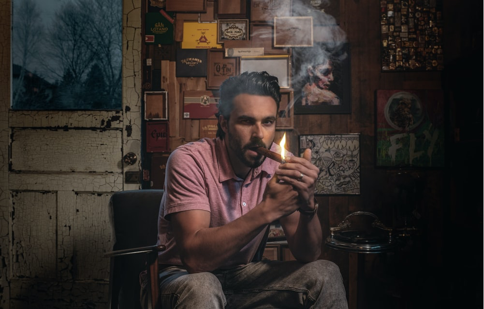 Man holding a flame up to his cigar