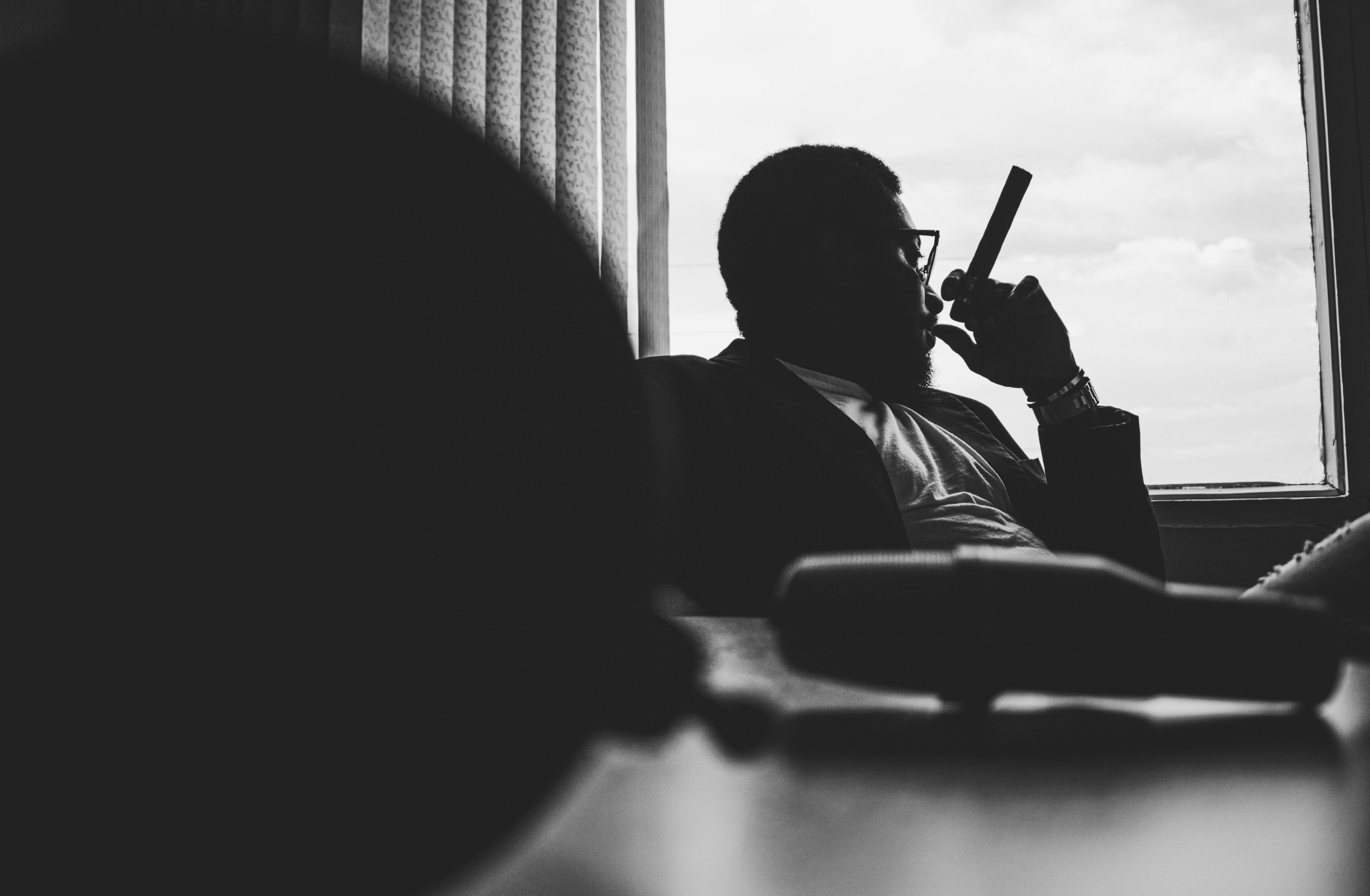 A man sitting by a window holding a cigar