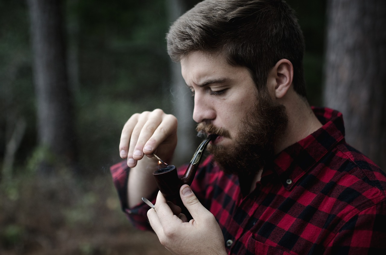 A man lighting a pipe outside