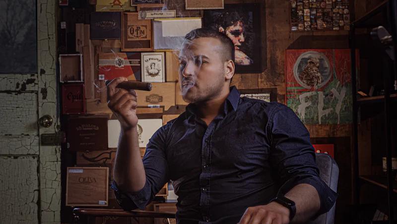 A man sat smoking a cigar