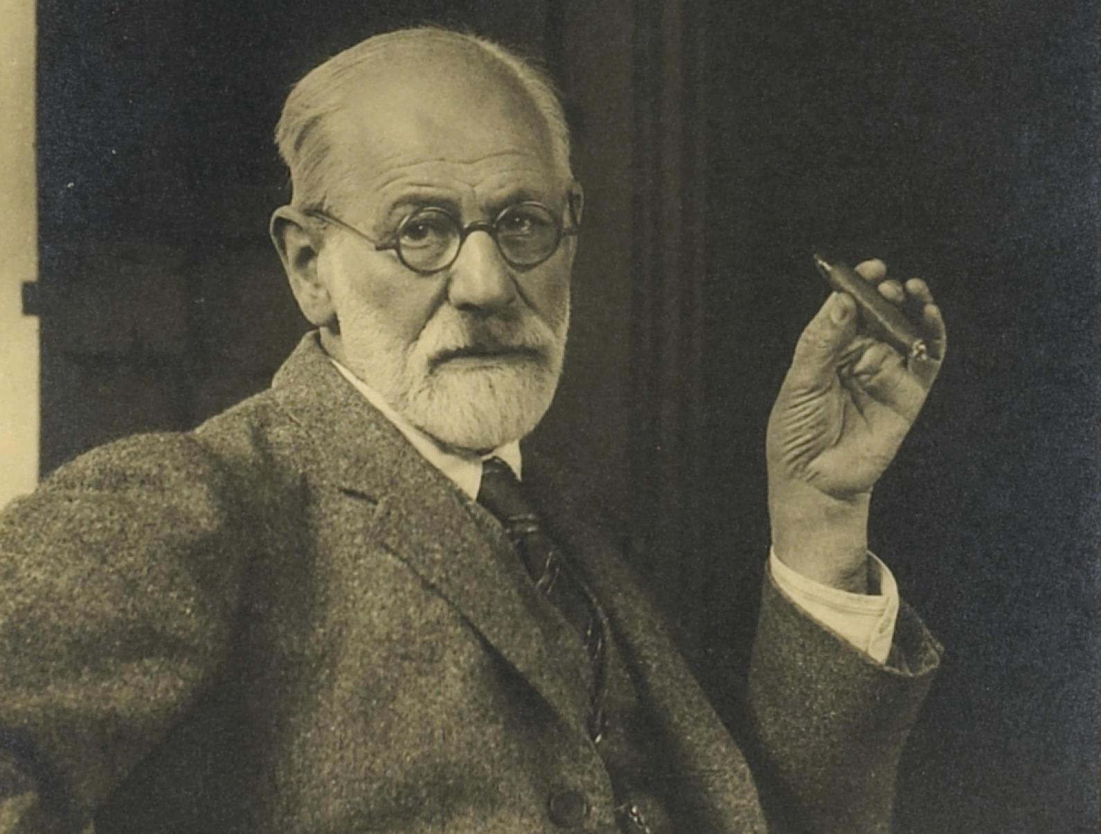 Sigmund Freud wearing glasses and smoking a cigar