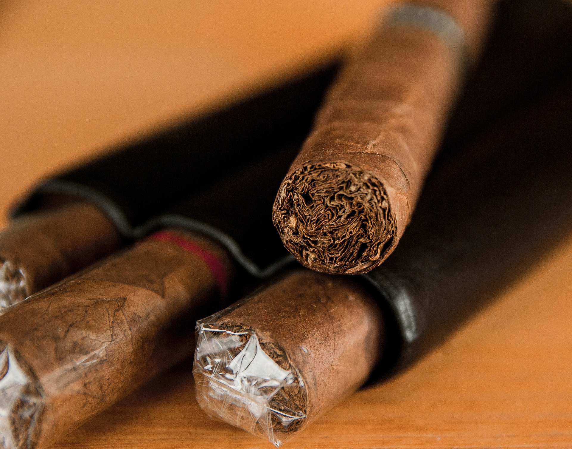 A pile of plastic wrapped cigars with an unwrapped cigar lying on top