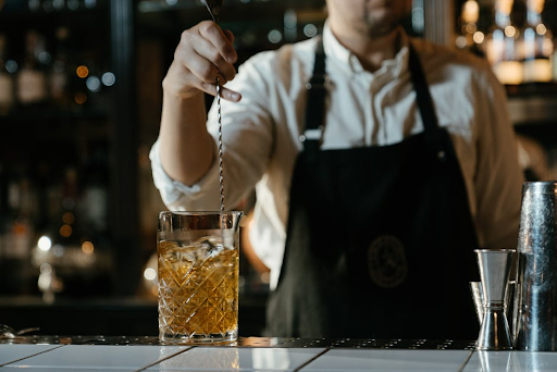 A man mixing an Old Fashioned at a bar